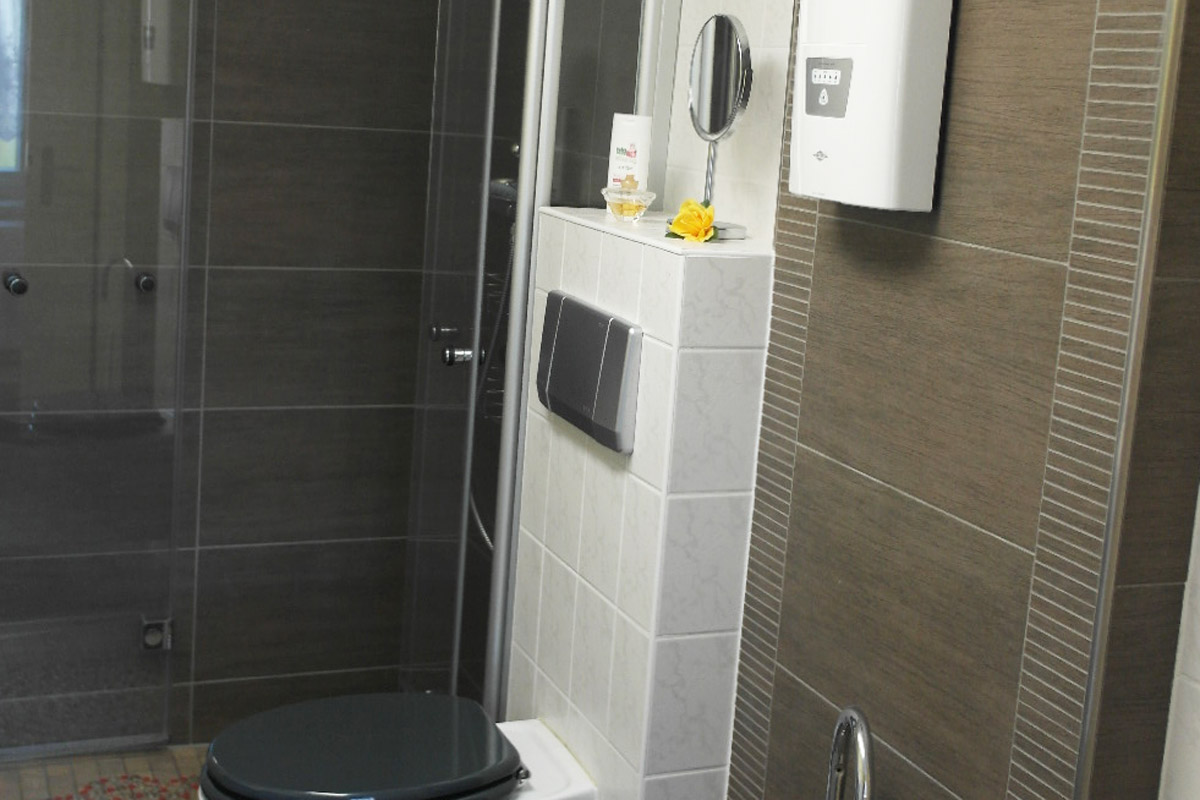Badezimmer mit Dusche, WC, Badewanne und Waschmaschine